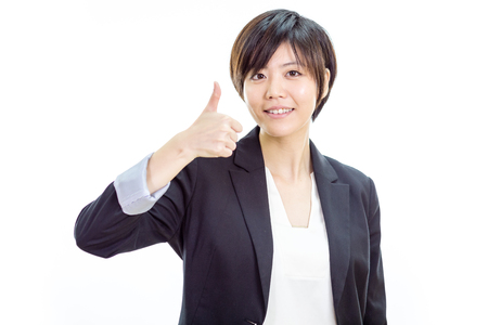 Chinese businesswoman in casual office clothes showing thumbs up Stock Photo