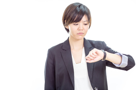 busineswoman: Chinese businesswoman in casual office clothes looking at watch Stock Photo