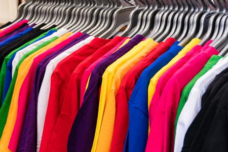 Colorful t-shirts on hangers on rack Foto de archivo