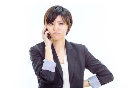 Chinese businesswoman in casual office clothes on cell phone looking annoyed