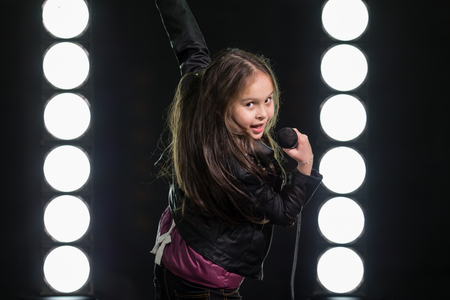 rockstar: Young rockstar girl singing in front of stage lights, looking over shoulder Stock Photo