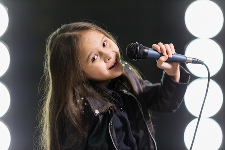 rockstar: Young rockstar girl on in stage with lights behind her Stock Photo