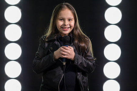 rockstar: Smiling young rockstar girl holding microphone Stock Photo