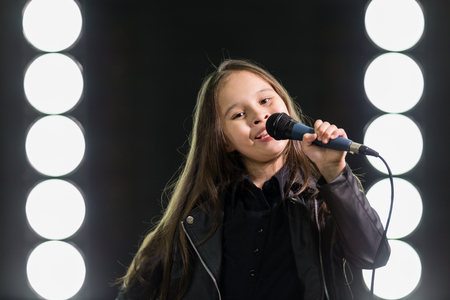 rockstar: Young rockstar girl singing in front of stage lights Stock Photo
