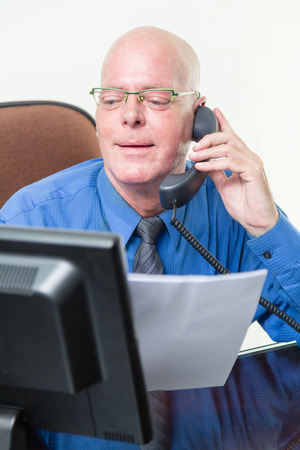 comparing: Corporate worker at desk comparing written notes with computer data