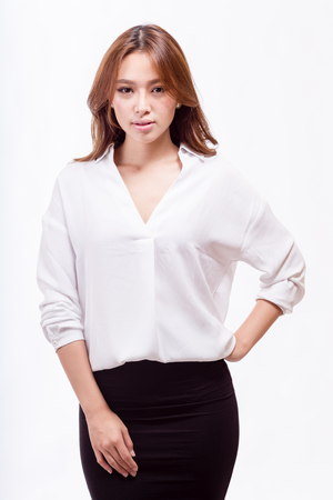 Attractive Asian American businesswoman in white blouse and black skirt looking at camera