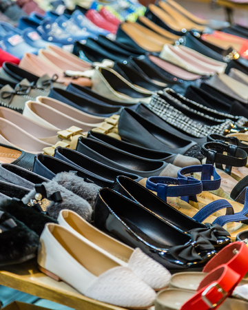Rows of shoes on a table, casual and formal Stock Photo