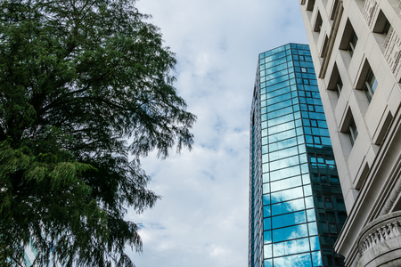 Modern glass building reflecting clouds and sky next to old style building