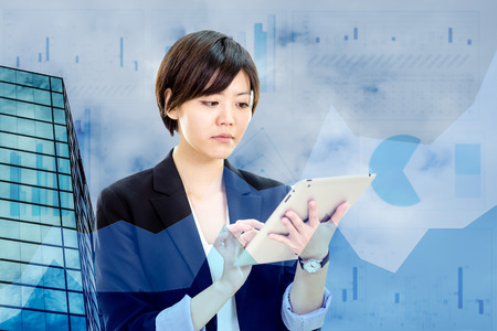 Chinese businesswoman in casual office clothes working on tablet computer with office, sky, and charts background and foreground