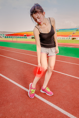 Asian woman jogger holding throbbing red painful leg on track