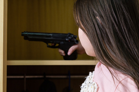 finds: Young child finds pistol in cupboard, gun control concept Stock Photo