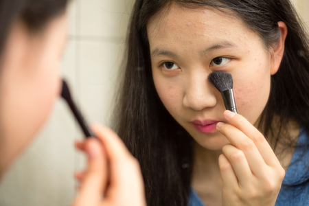 Chinese teenager putting on makeup with brush in front of mirror