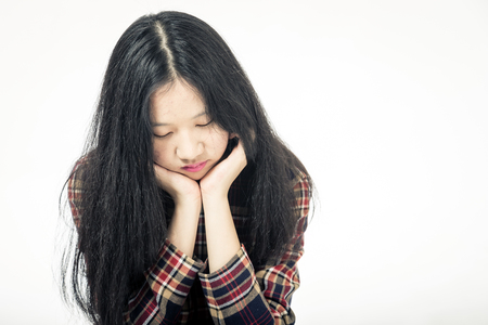 Chinese teenager sad with head in hands