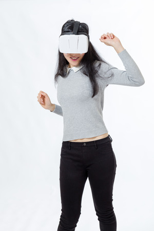 Teenage girl wearing 3D  VR goggles, dancing and smiling