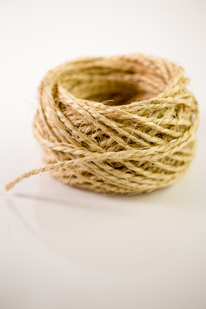Ball of twine unrravels on white background