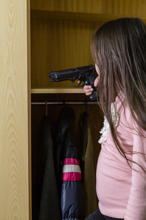 Young child finds pistol in cupboard, gun control concept Stock Photo