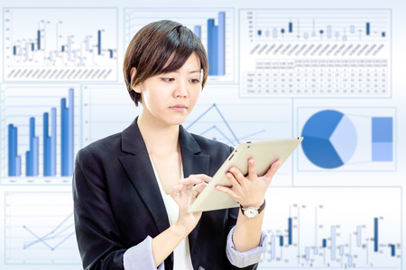 Chinese businesswoman in casual office clothes working on tablet computer with stock market charts background