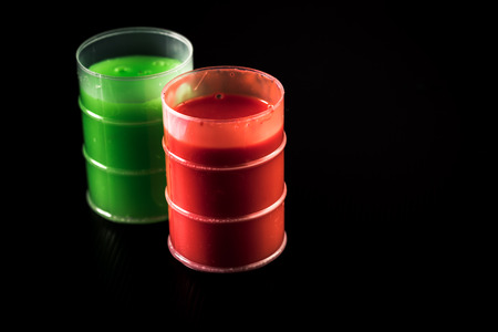 Green and orange barrels of slime on black background