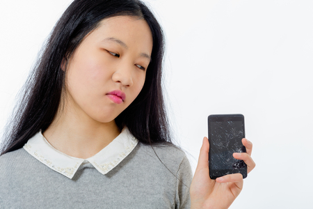Upset Chinese schoolgirl with cracked cellphone