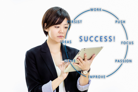Chinese businesswoman in casual office clothes working on tablet computer with success brainstorm Stock Photo
