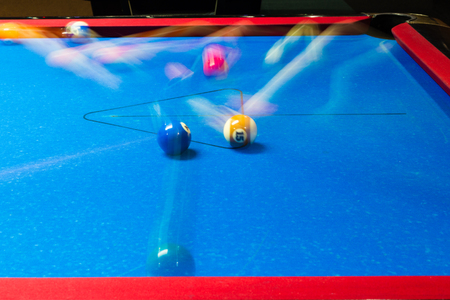 Motion blurred balls on a pool table with blue felt