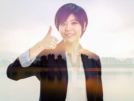 Chinese businesswoman in casual office clothes showing thumbs up with cityscape double exposure