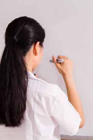 Chinese high school girl in uniform writing on whiteboard