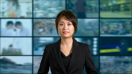 Asian American female news anchor in studio with screens in background