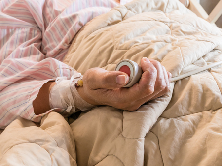 Woman pushing emergency button in hospital bed, health care concept