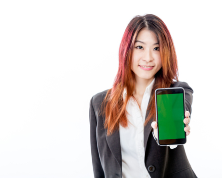 Defocused Asian woman holding out smartphone with green screen, copy space
