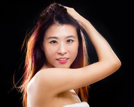 Asian woman with towel, low key black background