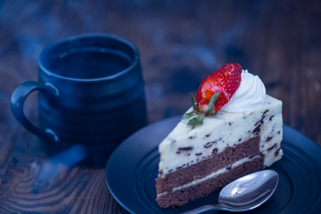 Steaming hot coffee and chocolate and cheese cake on wood background