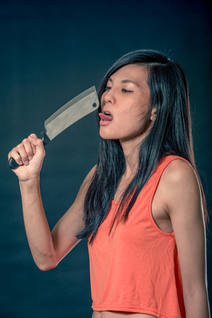 Sensual Chinese woman licking a chefs knife, filter look