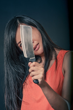 Sinister Chinese woman holding a chefs knife Stok Fotoğraf