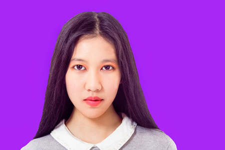 Portrait of Chinese teenage model on purple background looking at camera