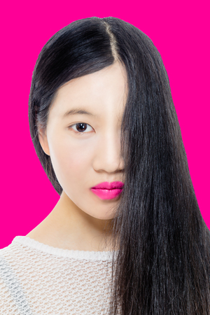 Teenage Asian American girl with hair covering half face on pink background