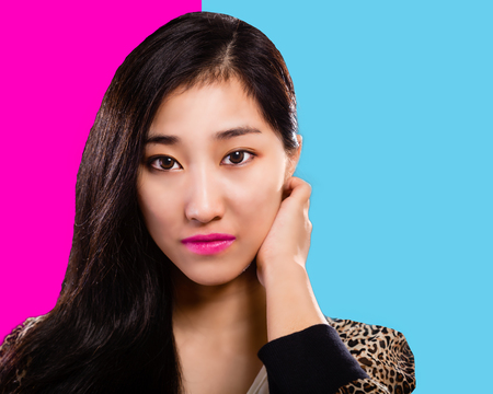 Asian fashion model with hand on face pink and turquoise background