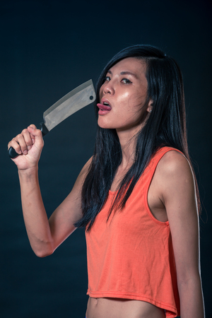 Sensual Chinese woman licking a chefs knife