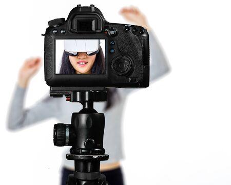Concentrez-vous sur la vue en direct sur la caméra sur un trépied, une adolescente utilisant une image de lunettes VR sur l'écran arrière avec une scène floue en arrière-plan. Concept de spectacle de diffusion en direct de vlogger pour adolescents