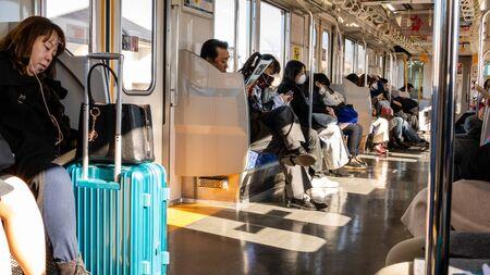 TOKYO, JAPAN - FEBRUARY 2, 2019: Commuters on train