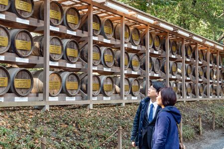 TOKYO, JAPAN - FEBRUARY 7, 2019: Unidentified people  looking at traditional sake barrels by Meiji Shrine.