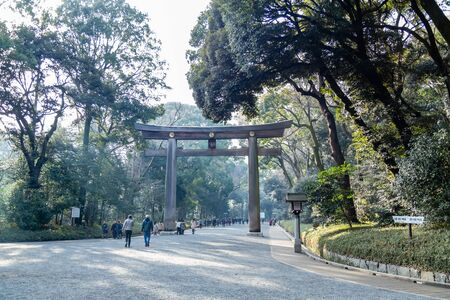 TOKYO, JAPAN - FEBRUARY 7, 2019: Unidentified people by torii gate of Meiji Shrine in Shibuya, Tokyo. The shrine is officially designated Kanpei-taisha, the 1st rank of government supported shrines.