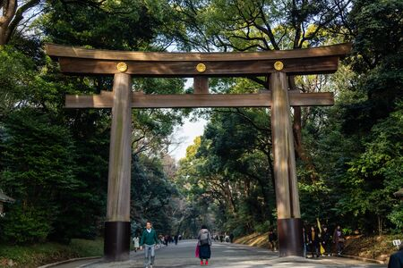 TOKYO, JAPAN - FEBRUARY 7, 2019: Crowds by torii gate of Meiji Shrine in Shibuya, Tokyo. The shrine is officially designated Kanpei-taisha, the 1st rank of government supported shrines.