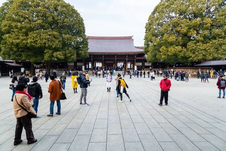 TOKYO, JAPAN - FEBRUARY 7, 2019: Crowds of tourists in Meiji Shrine in Shibuya, Tokyo. The shrine is officially designated Kanpei-taisha, the 1st rank of government supported shrines. Standard-Bild - 140208337