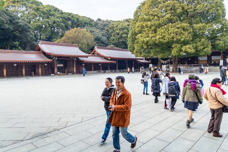 TOKYO, JAPAN - FEBRUARY 7, 2019: Crowds of tourists in Meiji Shrine in Shibuya, Tokyo. The shrine is officially designated Kanpei-taisha, the 1st rank of government supported shrines. Standard-Bild - 140208357