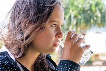 Tween girl drinks water with blurred beach background Standard-Bild