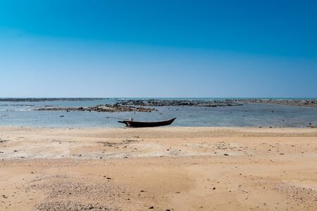 Longboat on sandy tropical beach with rocks in background