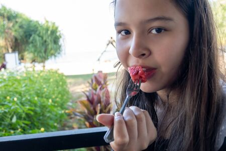 Asian American Tween girl eats watermelon with a fork