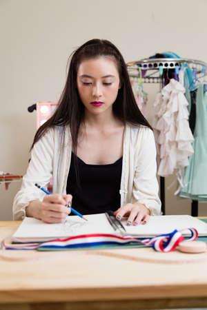Young Asian American fashion designer sketching design