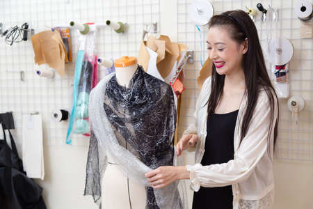 Asian American fashion designer dressing a mannequin